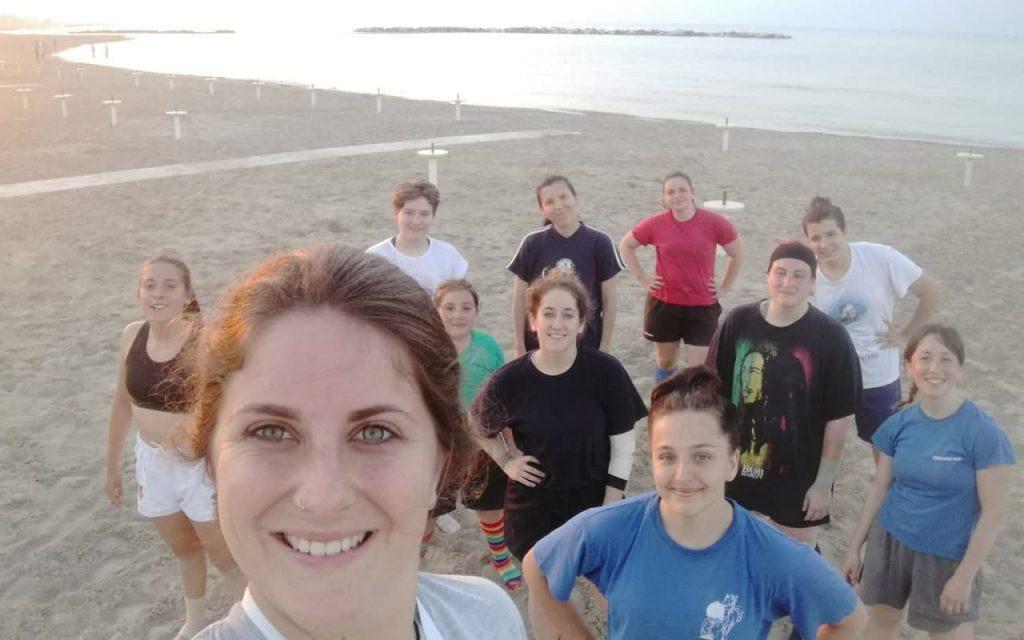 Foto di gruppo delle ragazze del rugby femminile Le Pellerossa sulla spiaggia di Rimini con il mare alle spalle